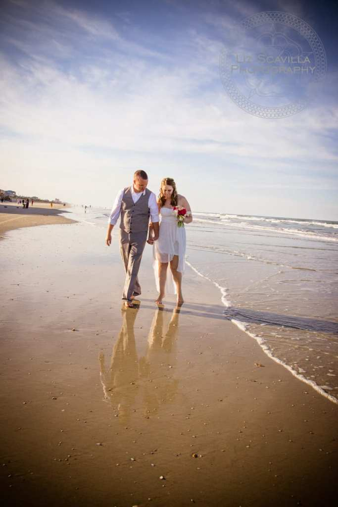 Newlyweds Walking Along Beach