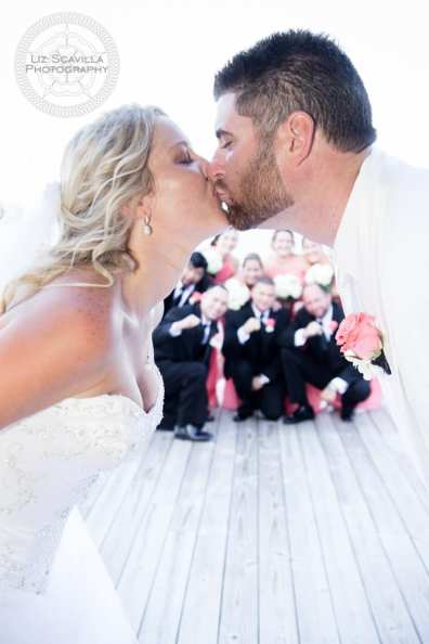 Wedding Party Behind Kissing Couple
