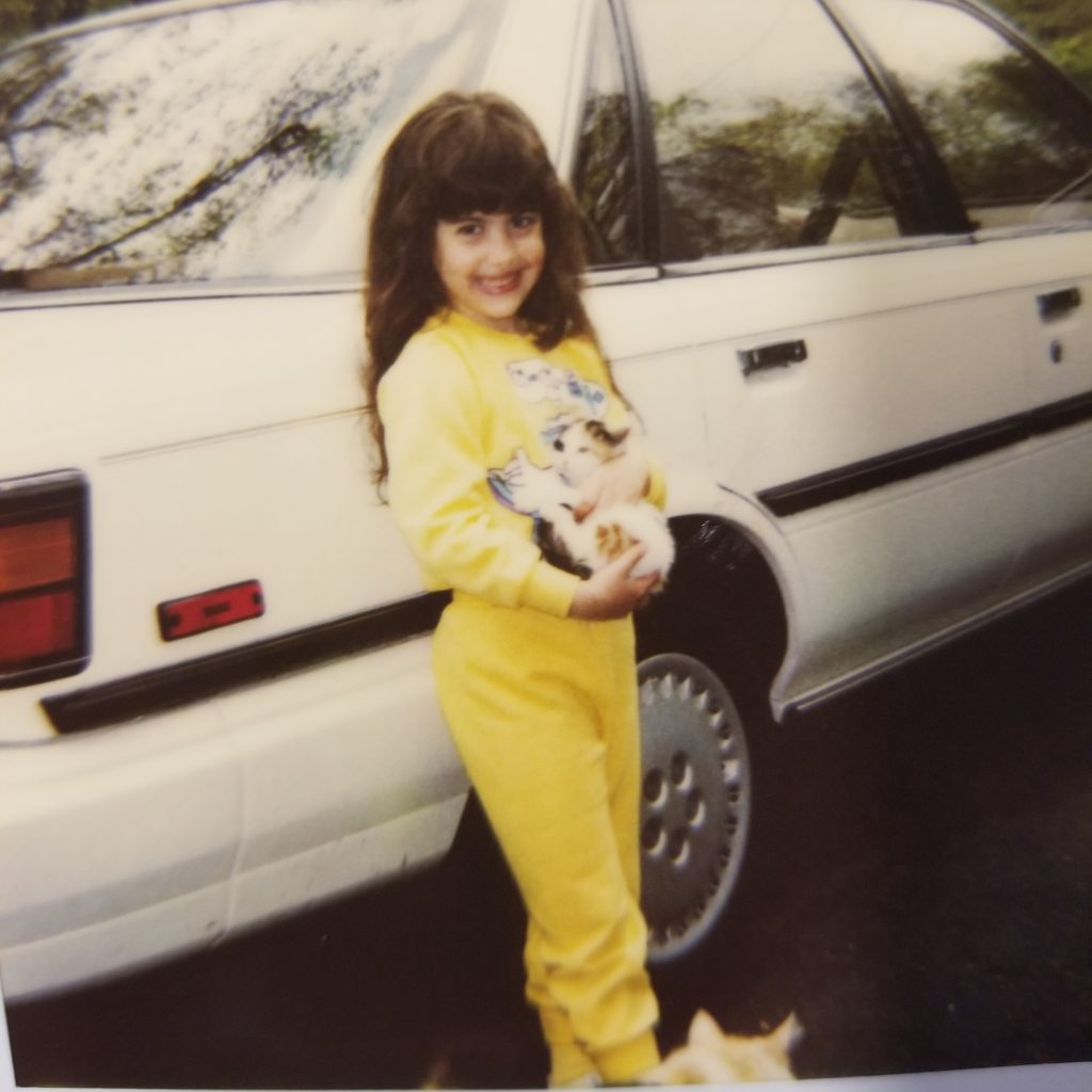 Girl in sweatsuit holding kitten next to car