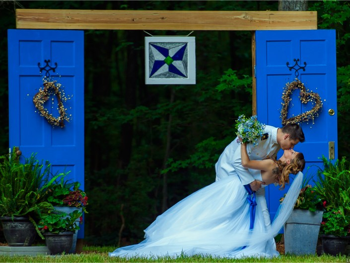 Navy Wedding. New bride and groom share a kiss in front of their unique, custom made wedding alter.