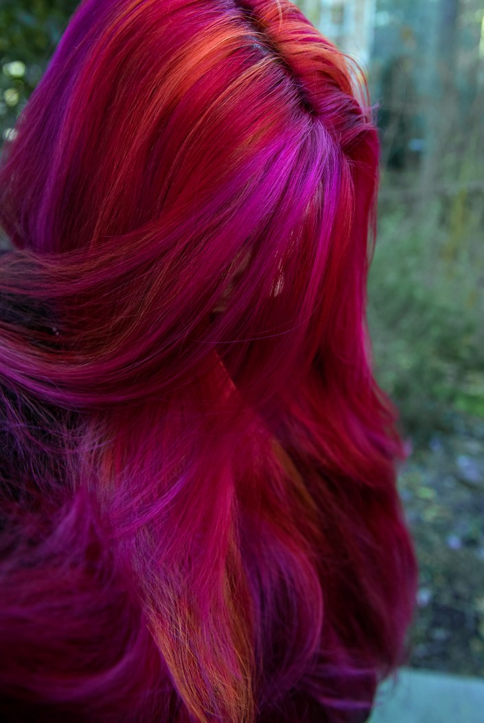 A mix of red hair with pink and orange streaks by Lizzy Davis.