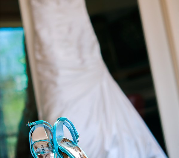 Turquoise wedding shoes with a wedding dress in the background.