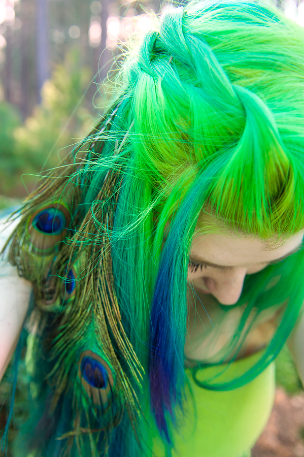 Vibrant green hair with blue and purple peacock accents.