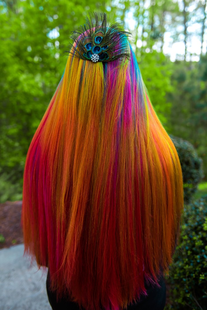 Long orange hair with rainbow highlights and peacock hair clip.