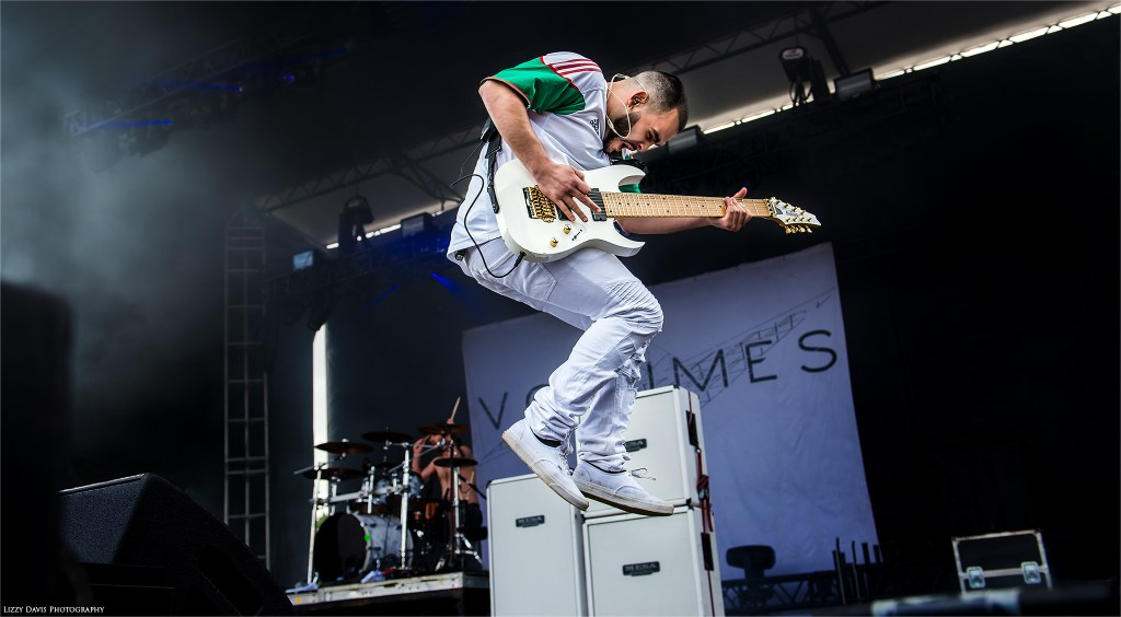 Volumes guitarist Diego Farias jumping on stage at Carolina Rebellion. ©Lizzy Davis Photography