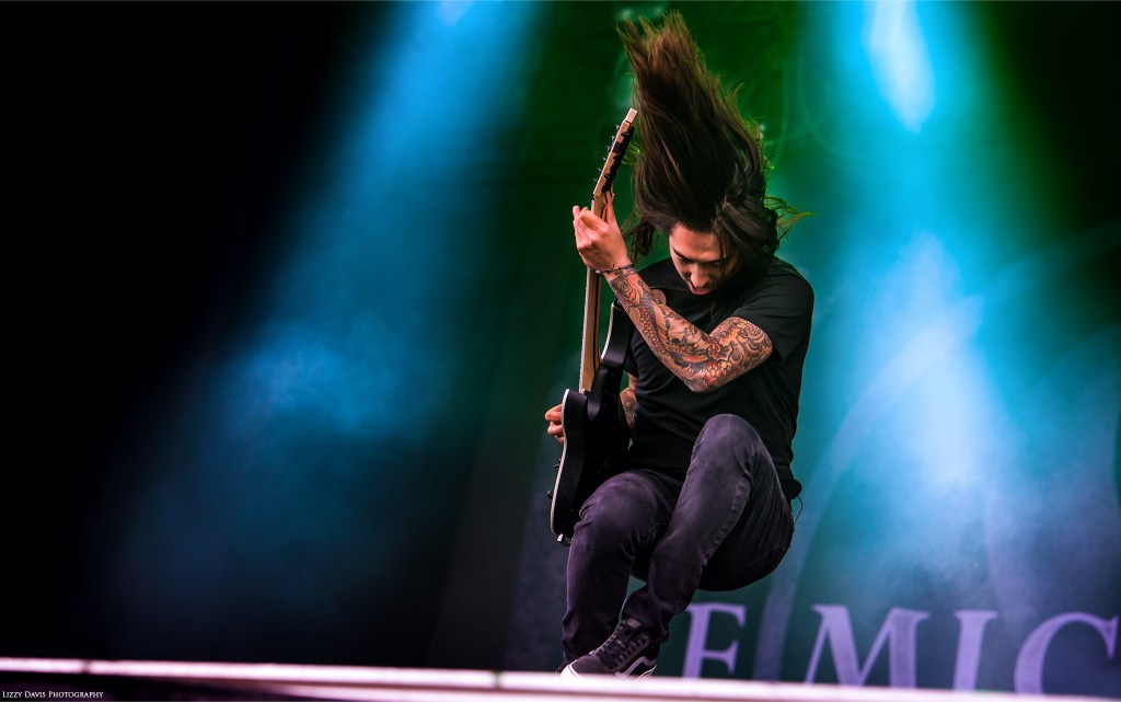 Of Mice & Men guitarist Phil Manansala jumping off a riser at Carolina Rebellion. ©Lizzy Davis Photography
