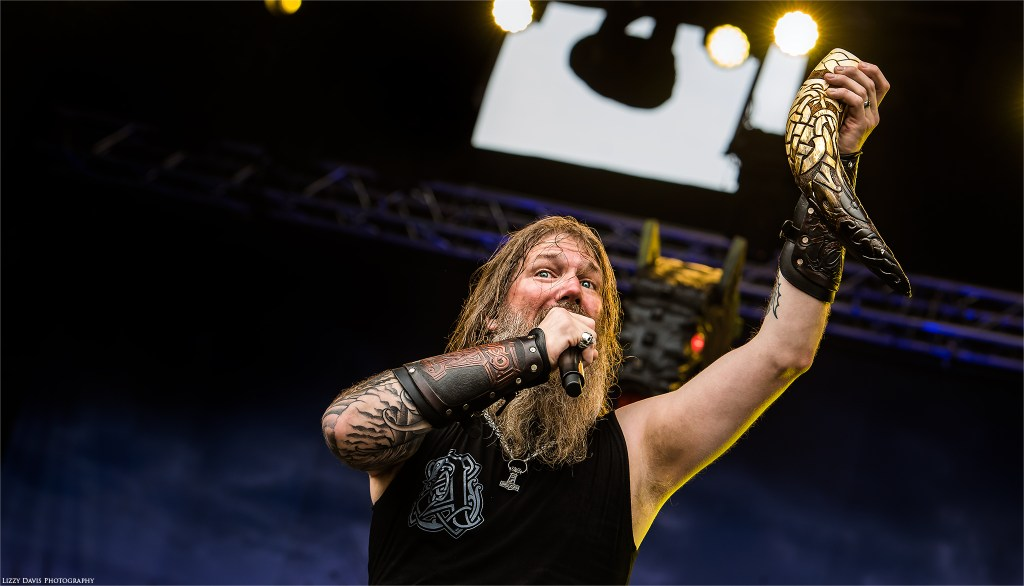 Vocalist Johan Hegg of Amon Amarth cheers to the crowd with his Viking horn.
