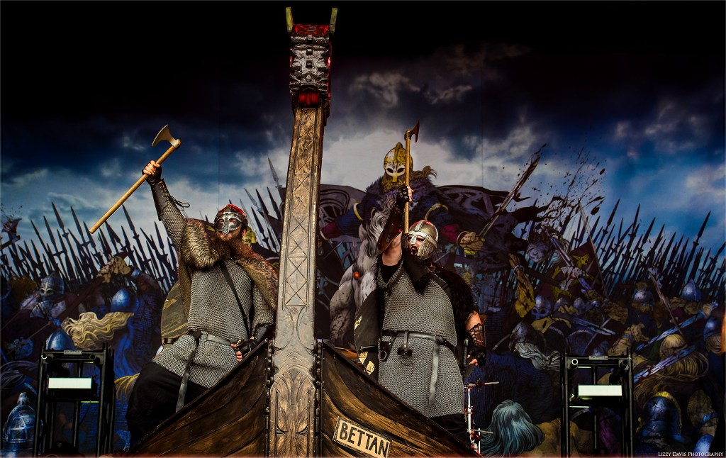 The Vikings invade Amon Amarth's ship with axes held high.