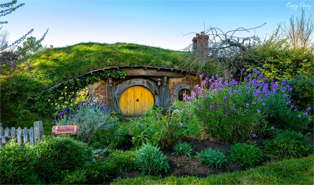 Photo of a Hobbit-hole with a yellow door inside Hobbiton.
