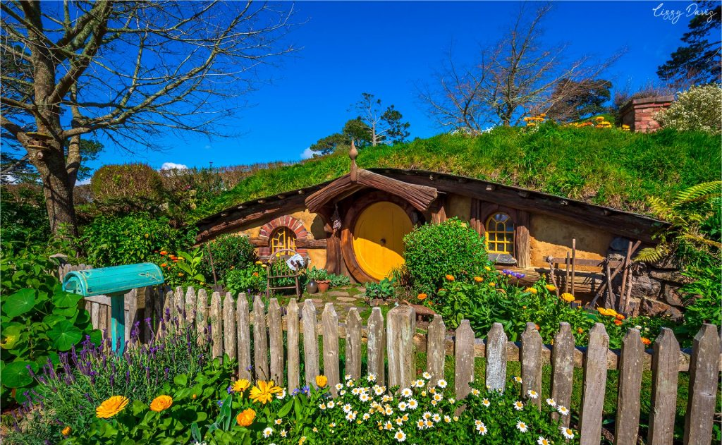 Vibrant colored hobbit-hole with turquoise mailbox.