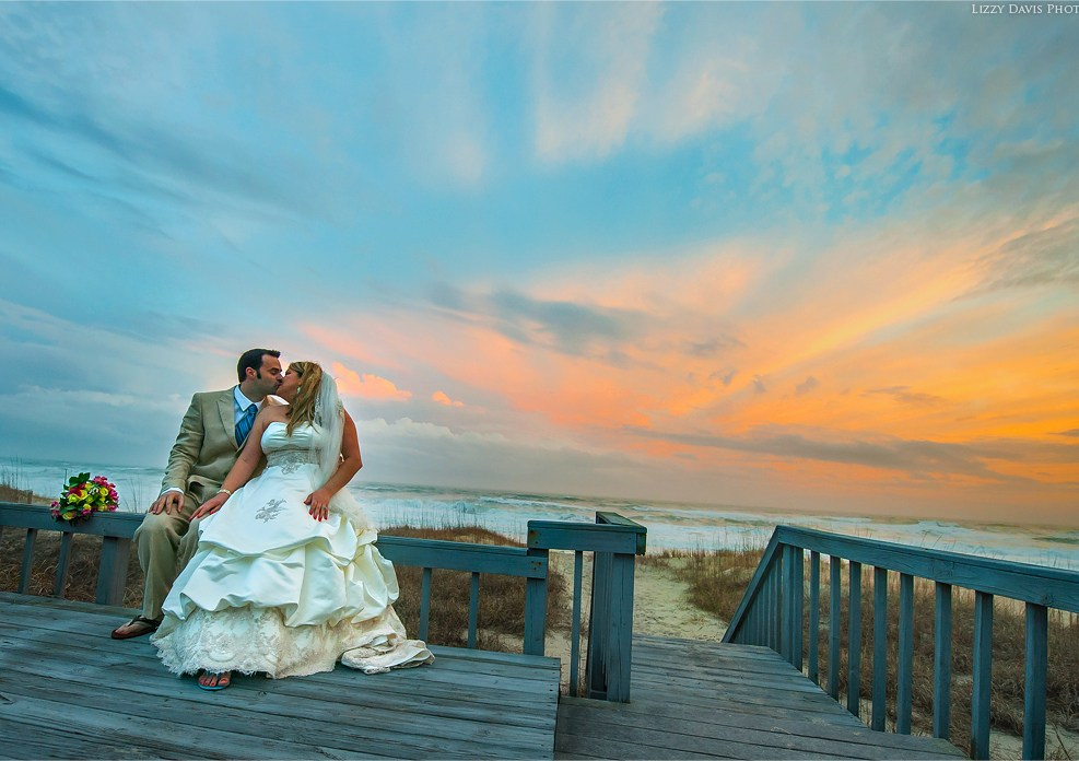 Photo of newlyweds sharing a kiss during sunset over Emerald Isle Beach in North Carolina.