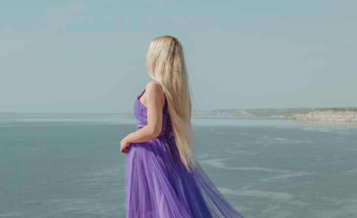 anonymous elegant model in purple dress contemplating sea from mount