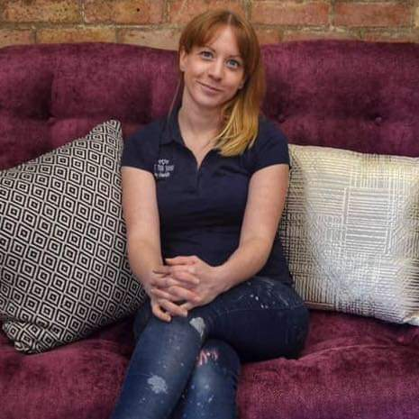 image of charlotte williams a white woman with long hair wearing paint splattered jeans and a navy top sitting on a purple sofa - email-marketing-copywriter-nottingham