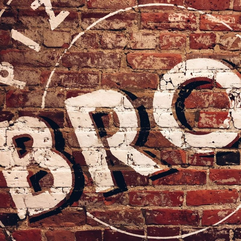 bro ethical marketing, white painted letters on a red brick wall