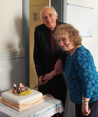 Rector and wife cutting their retirement cake.