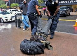 Occupy Wall Street man on ground being arrested being dragged by his leg 02