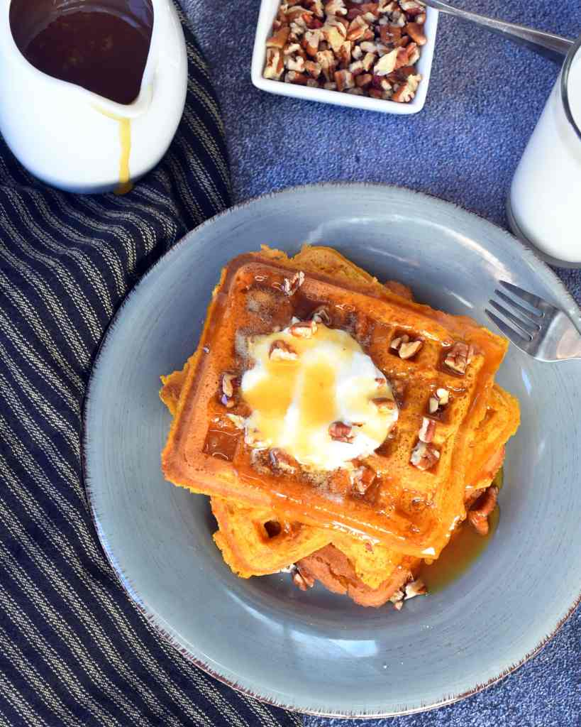pumpkin waffles topped with whipped cream, pecans, syrup on a blue plate with syrup in a white pitcher on the side
