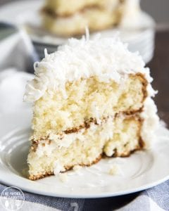 A slice of coconut cake on a white plate. It's a light colored cake, topped with a white frosting, and sweetened coconut.