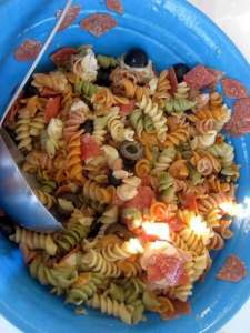 A simple colorful pasta salad using tricolor rotini noodles; adding pepperoni and mozzarella cheese topped with Italian dressing for a simply perfect side dish.