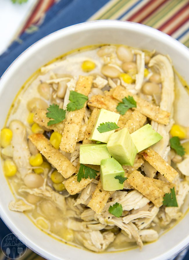 White Chicken Chili - This simple white chicken chili is packed full of flavor with shredded chicken, corn, white beans, and more. Top it with tortilla strips, avocado, and cilantro!
