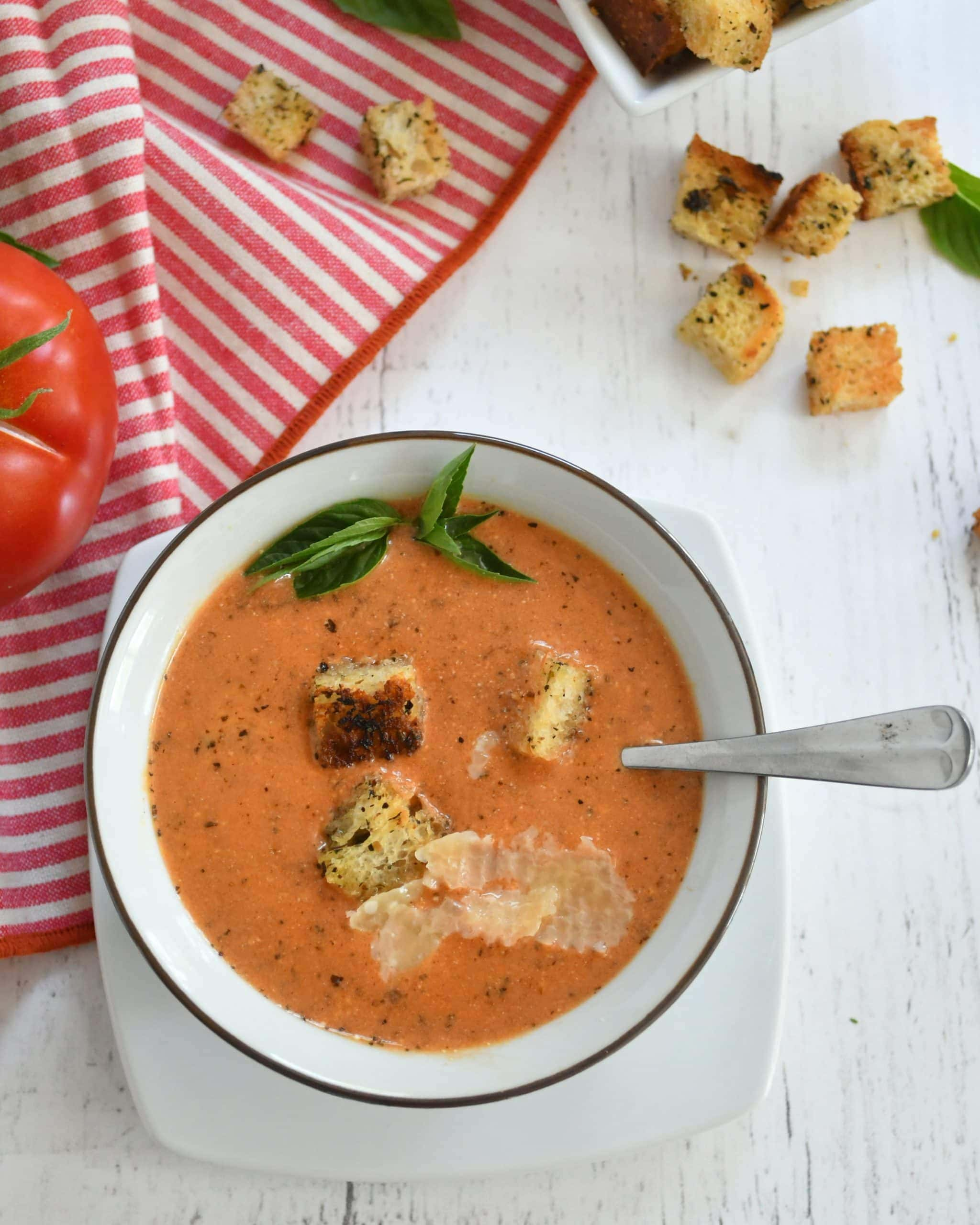 Tomato basil soup in a bowl with a spoon; topped with fresh basil, croutons,and Parmesan cheese; with a red and white napkin nearby and a red tomato, all framed with croutons sprinkled about