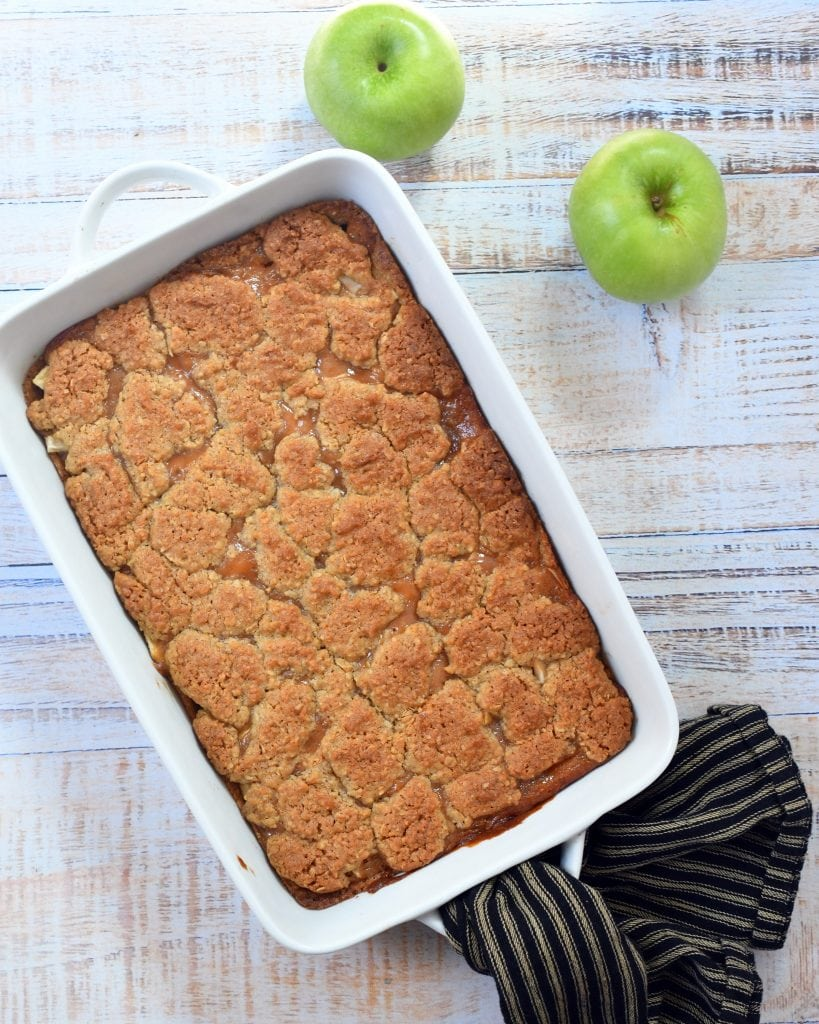 Caramel apple bar dessert in white baking pan with green apples by side