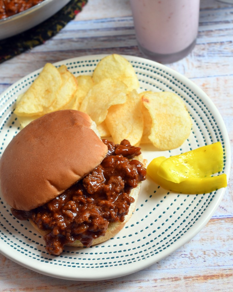 Sloppy Joe sandwich on a beige plate with potato chips, pickles plus a glass of raspberry shake