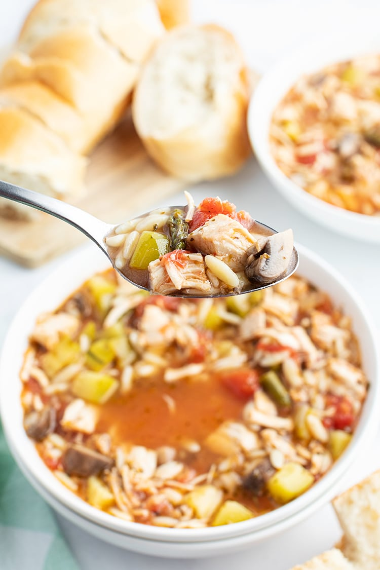 A spoonful of Italian Turkey and Orzo soup being taken out of the bowl.