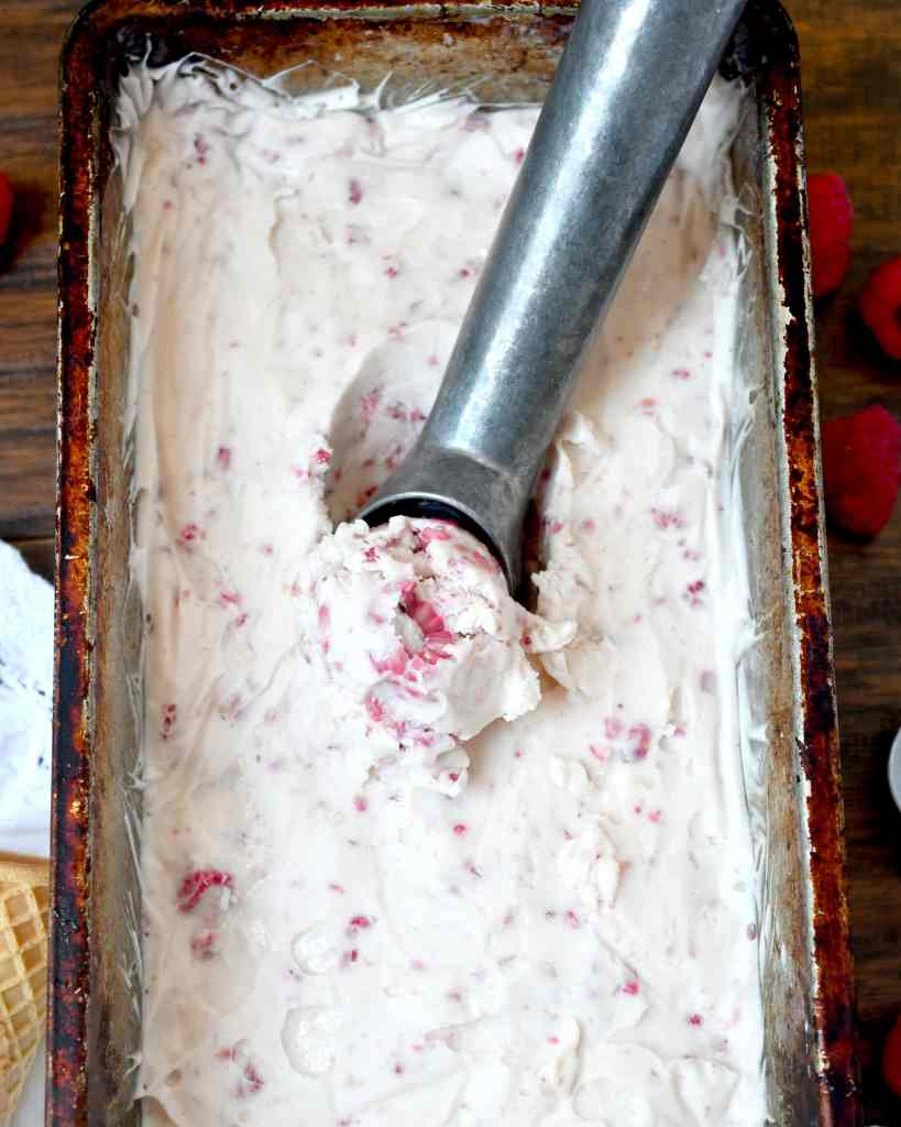 raspberry ice cream being scooped in a loaf pan