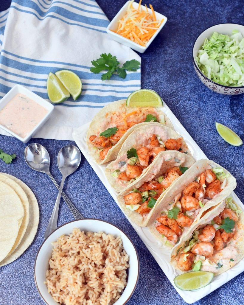 Shrimp tacos on a white plate with limes, cabbage, yogurt sauce, rice, and tortillas
