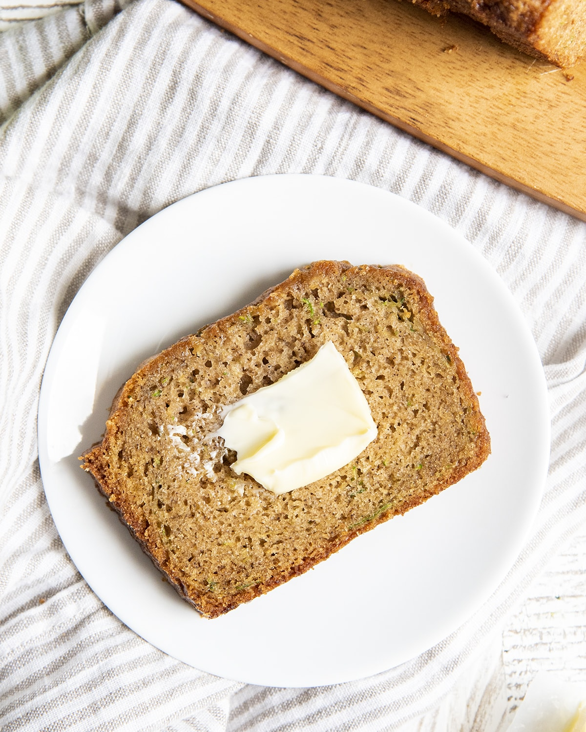 A piece of zucchini bread on a white plate with butter spread on it.