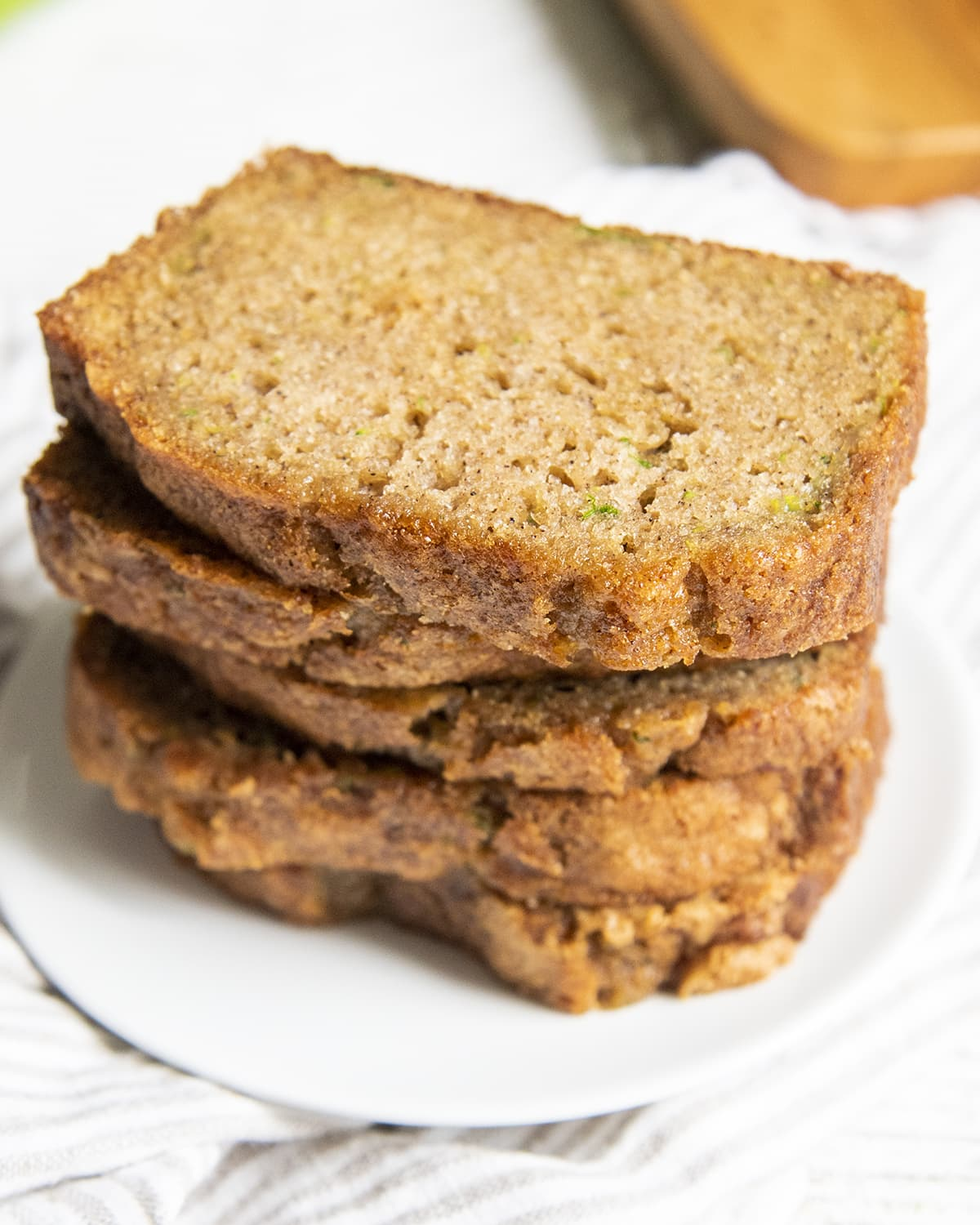A stack of sliced zucchini bread pieces on a white plate.