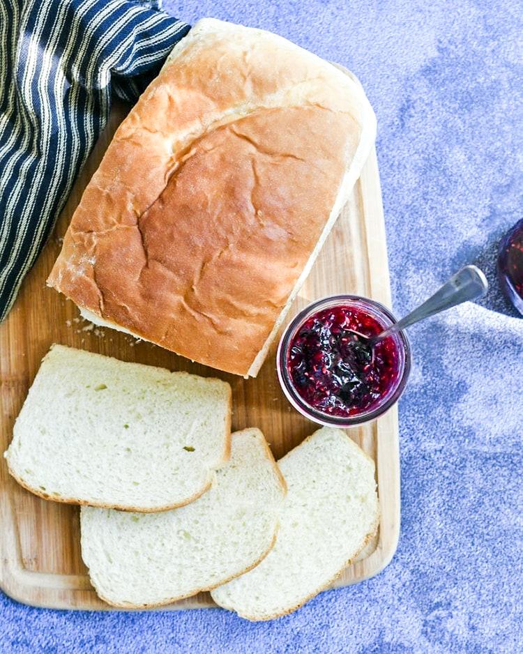 Raspberry blueberry jam in a jar alongside sliced bread