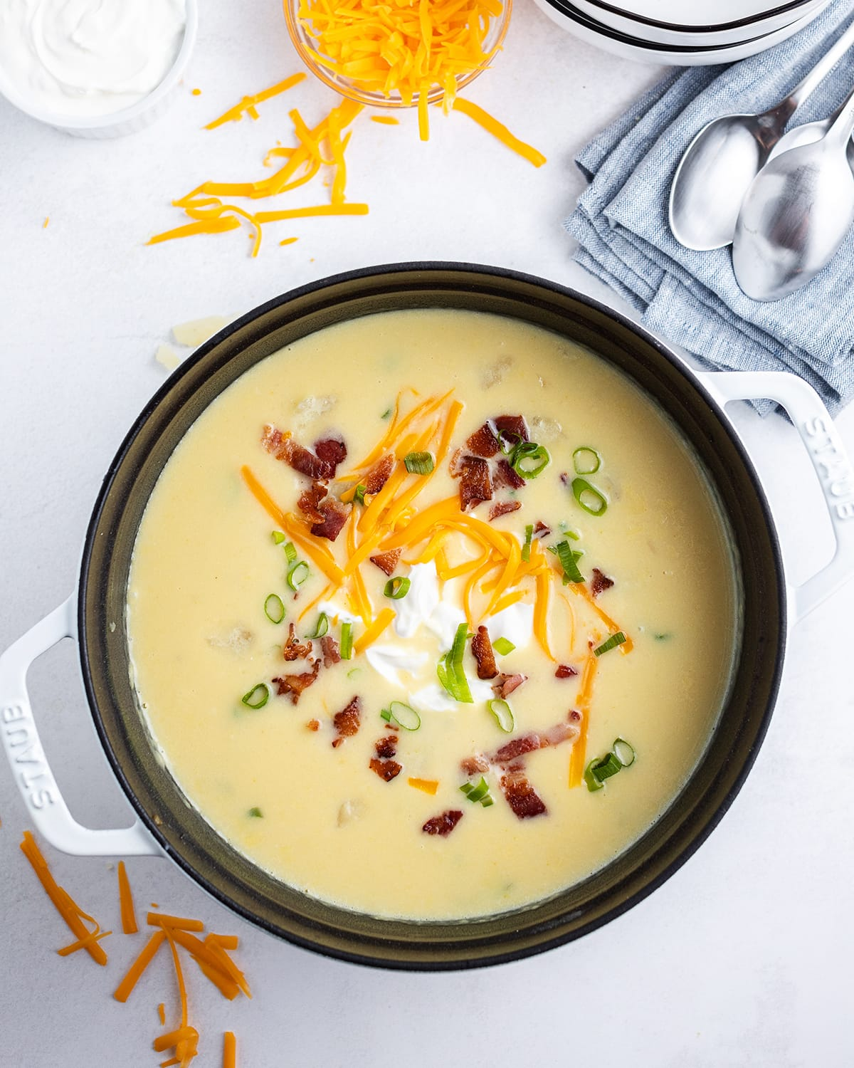 A pot of baked potato soup topped with sour cream, shredded cheese, crumbled bacon, and green onion.