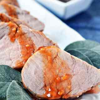 slices of pork tenderloin drizzled with peach honey sauce framed with sage leaves on a white serving dish