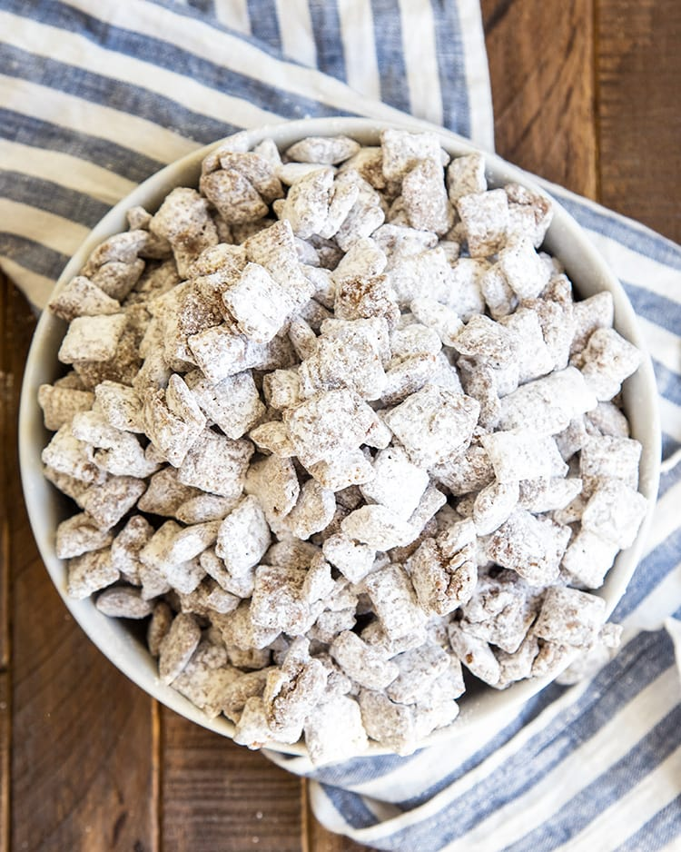 A white bowl full of muddy buddies with a blue and white striped cloth underneath it.