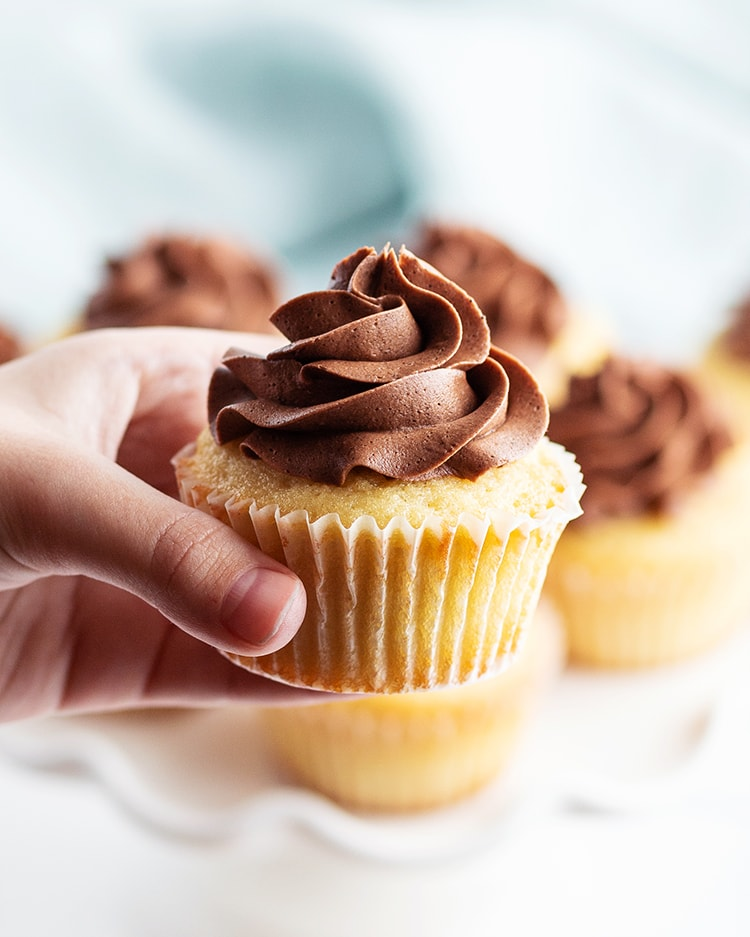 A hand holding a yellow cupcake with chocolate frosting on top.