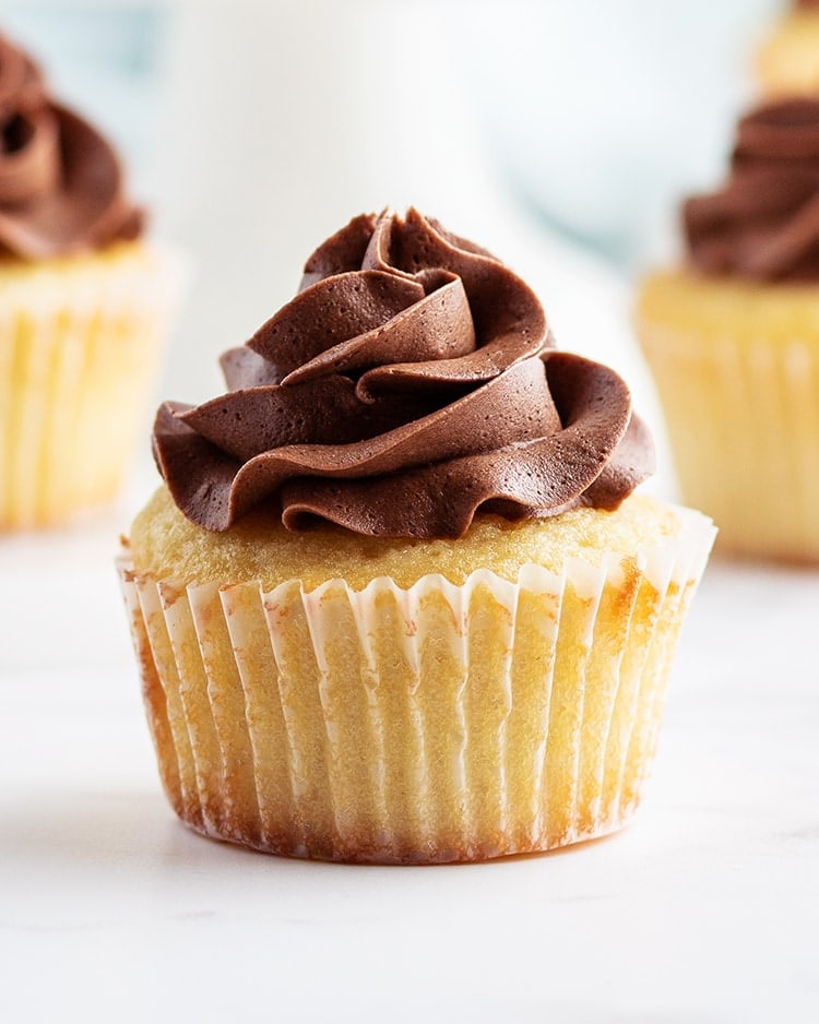 A close up of a yellow cupcake in a cupcake liner with a swirl of chocolate butter cream frosting on top.