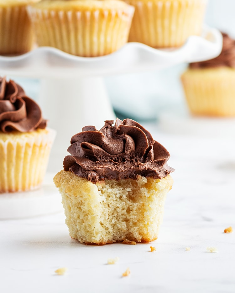 A classic yellow cupcake with chocolate frosting on top, with a bite taken out of it, showing the inside of the cupcake.