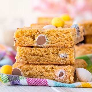 A stack of 3 blondies full of Cadbury Mini Eggs.