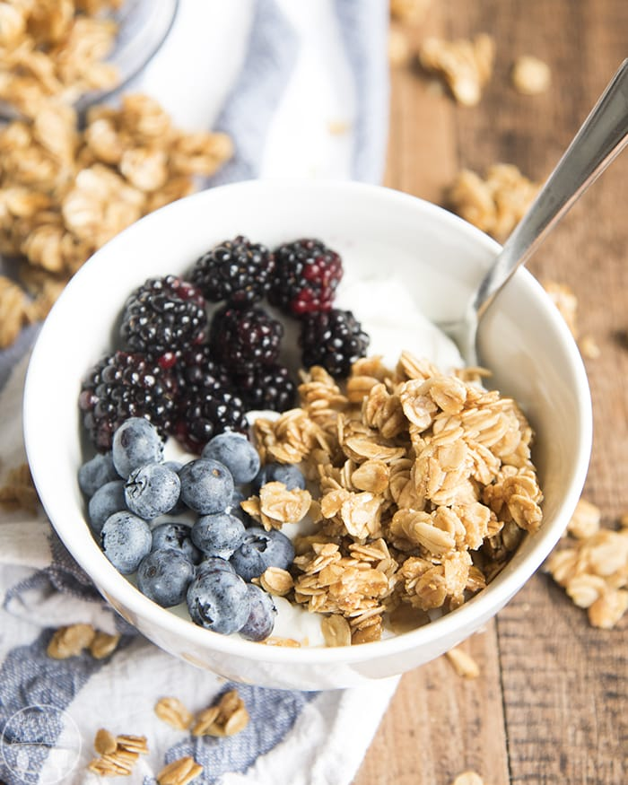 A bowl of yogurt topped with granola, blackberries, and blueberries.