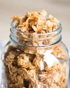 A close up of simple granola filled to the brim of a large mason jar.