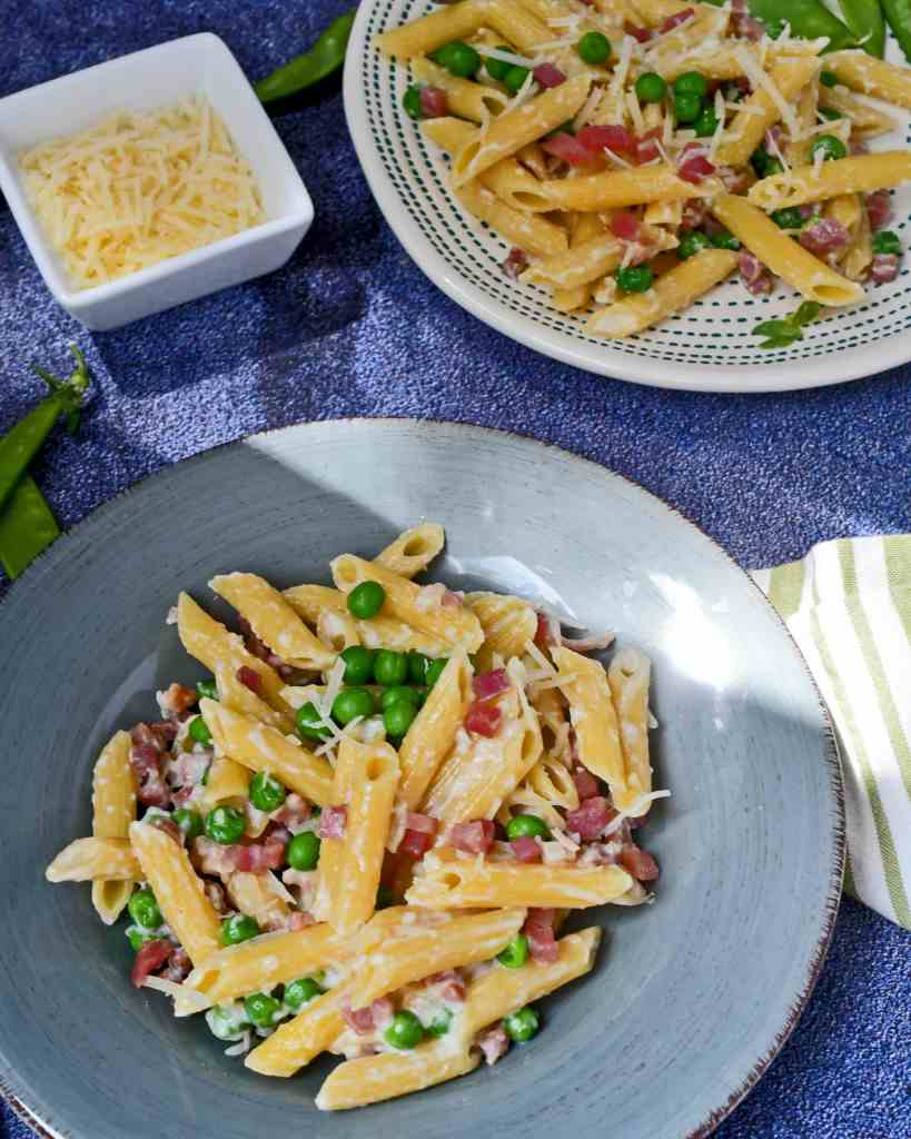 Two plates of penne pasta in a cream sauce with ham and green peas on plates with a small bowl of parmesan cheese on the side