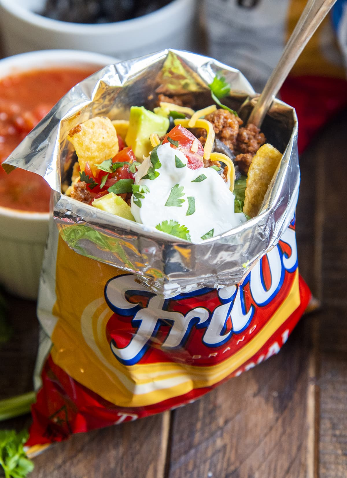 A walking taco in a frito bag with a fork in the bag.