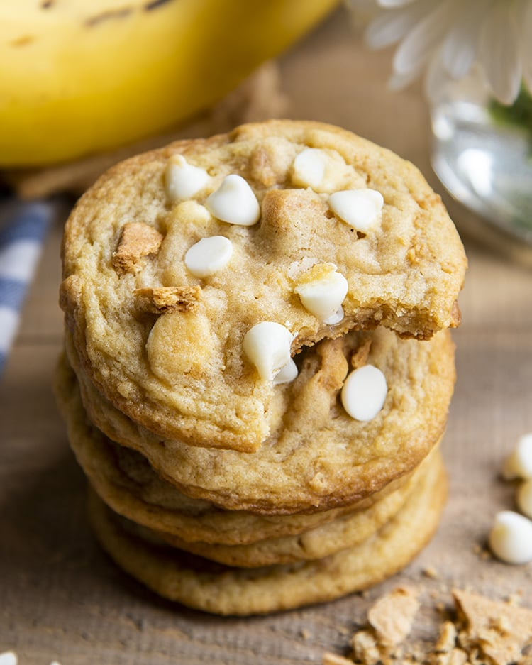 A stack of 4 banana cream pie cookies that are full of and topped with white chocolate chips and graham cracker pieces. There are bananas in the background of the photo. The top cookie has a bite taken out of it.