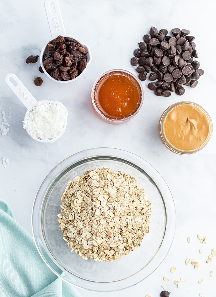 The ingredients needed to make granola bar bites in small bowls and measuring cups. There is a big bowl of old fashioned oats, shredded coconut, raisins, honey, peanut butter, and chocolate chips.