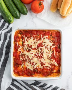 A white square baking dish full of zucchini lasagna shot from above. You can see the red sauce and sprinkles of baked shredded cheese over the top.