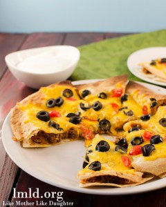 This Mexican Pizza uses 2 layered tortillas stuffed with taco meat, refried beans, and topped with cheese,olives, tomatoes, and lettuce.