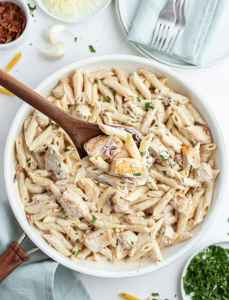 A Pasta dish in a pan with penne noodles and chicken in a white sauce. Topped with a sprinkle of parsley.