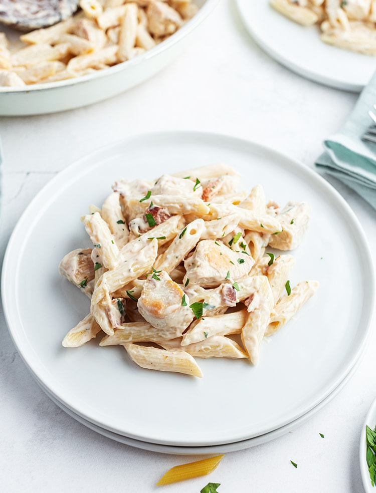 An alfredo pasta on a white plate, with penne noodles, chicken pieces, and a white sauce, the top is sprinkled with chopped parsley.